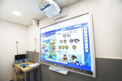 Clase de una academia de inglés cambridge english systems en parets del vallés, con sillas azules y mesa grande para alumnos.